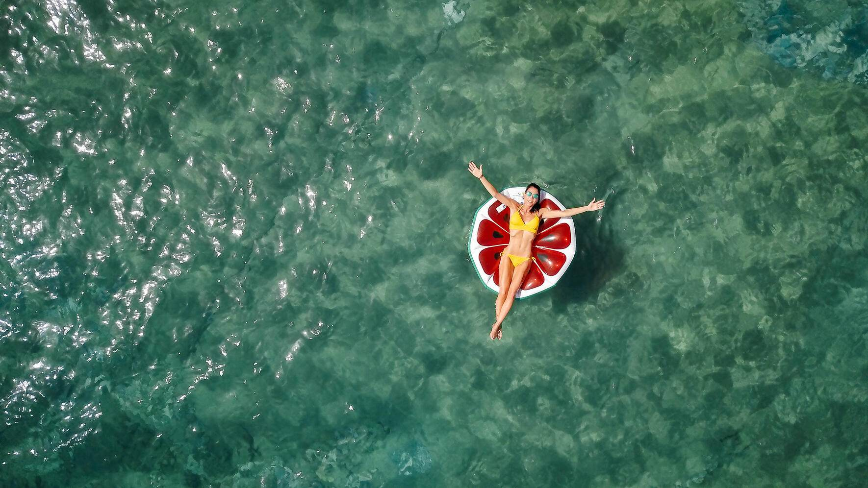 Young white woman with yellow bikini and sunglasses relaxing on watermelon shaped inflatable bed on the sea. Aerial drone footage. Turquoise mediterranean sea in Turkey, Alanya.