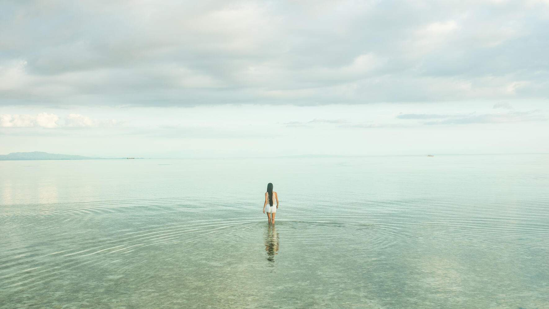 Full lenght rear view on young woman in sea water