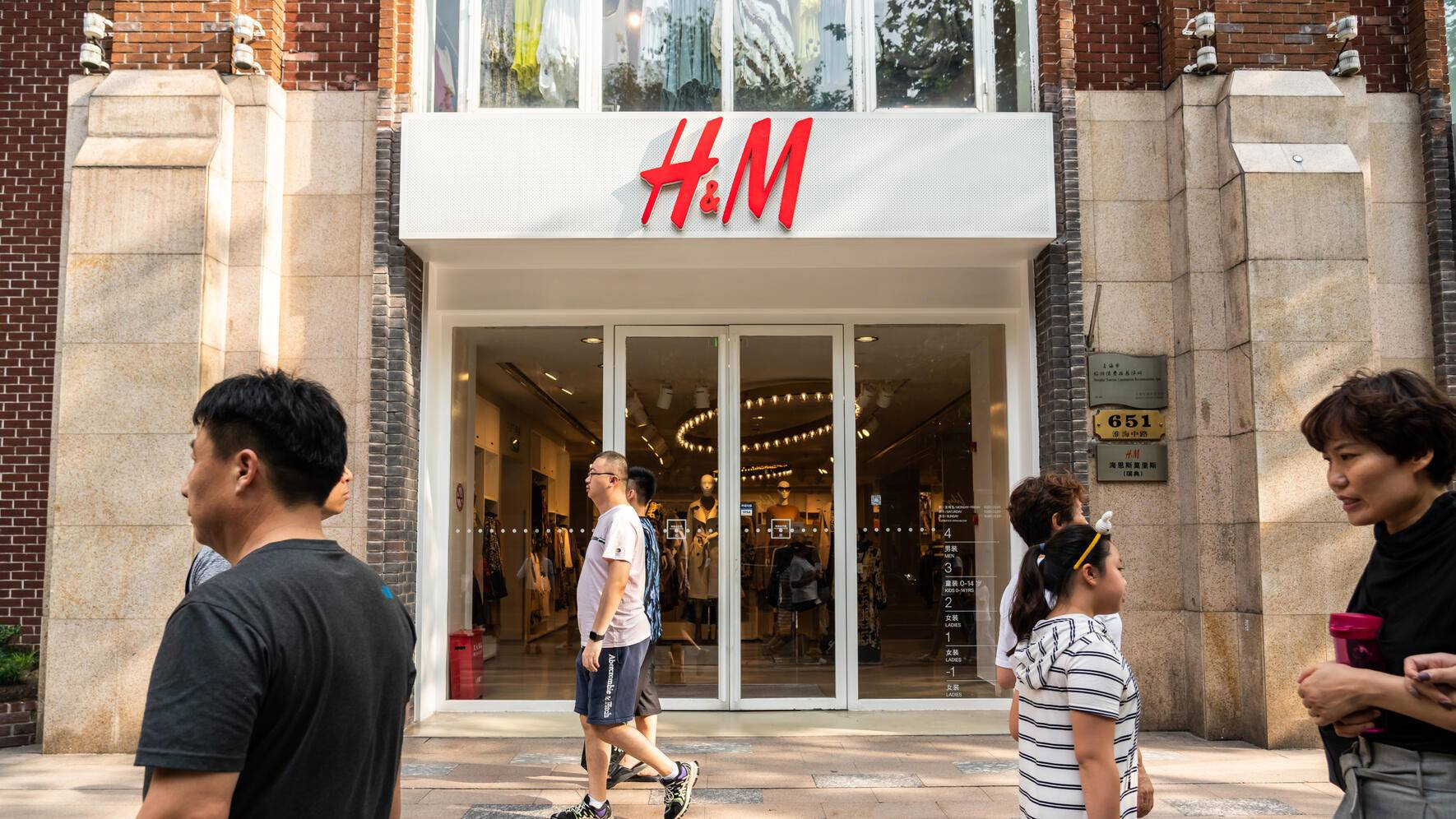 SHANGHAI, CHINA - 2019/09/07: Pedestrians walk past a Swedish multinational clothing-retail company Hennes & Mauritz, or H&M, store in Shanghai. (Photo by Alex Tai/SOPA Images/LightRocket via Getty Images)