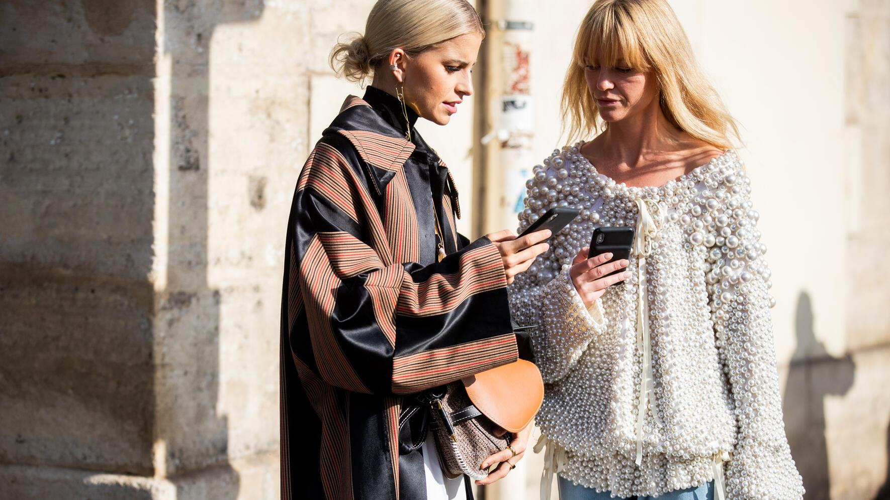PARIS, FRANCE - SEPTEMBER 27: Caroline Caro Daur and Jeanette Friis Madsen on their smartphone seen outside Loewe during Paris Fashion Week Womenswear Spring Summer 2020 on September 27, 2019 in Paris, France. (Photo by Christian Vierig/Getty Images)