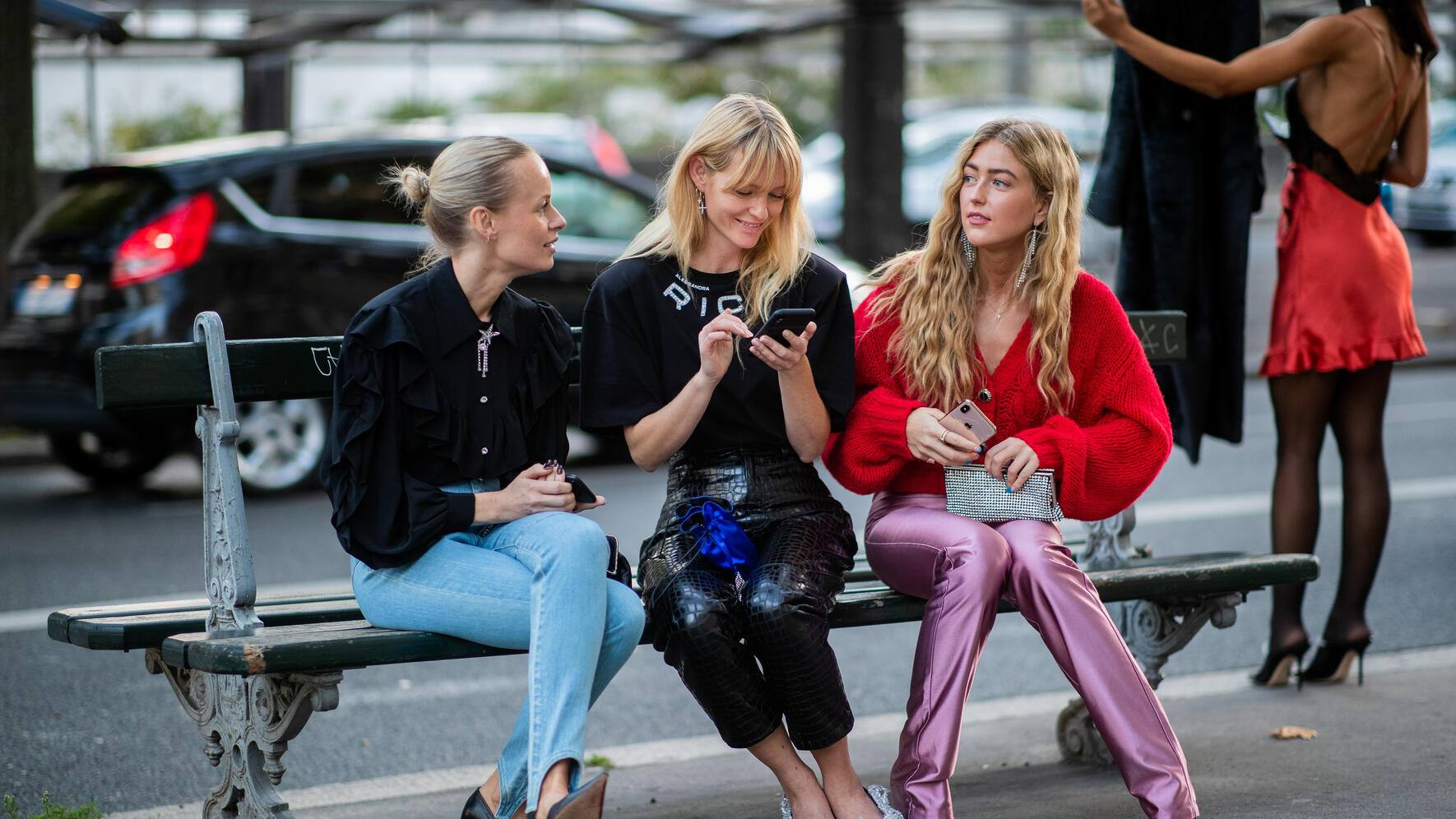 PARIS, FRANCE - SEPTEMBER 27: Thora Valdimars wearing denim jeans, black top and Jeantte Friis Madsen wearing shirt with logo print, black leather pants and Emili Sindlev wearing red knit, pink pants seen sitting on a bench checking their phone outside Alessandra Rich during Paris Fashion Week Womenswear Spring Summer 2020 on September 27, 2019 in Paris, France. (Photo by Christian Vierig/Getty Images)