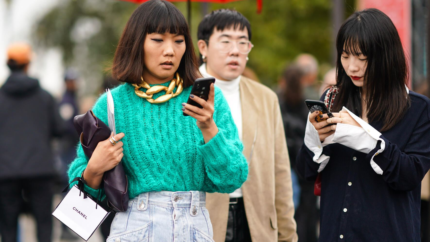 PARIS, FRANCE - OCTOBER 01: A guest wears a green wool knitted pullover, a large chain golden necklace, denim pants,  outside Chanel, during Paris Fashion Week - Womenswear Spring Summer 2020, on October 01, 2019 in Paris, France. (Photo by Edward Berthelot/Getty Images)