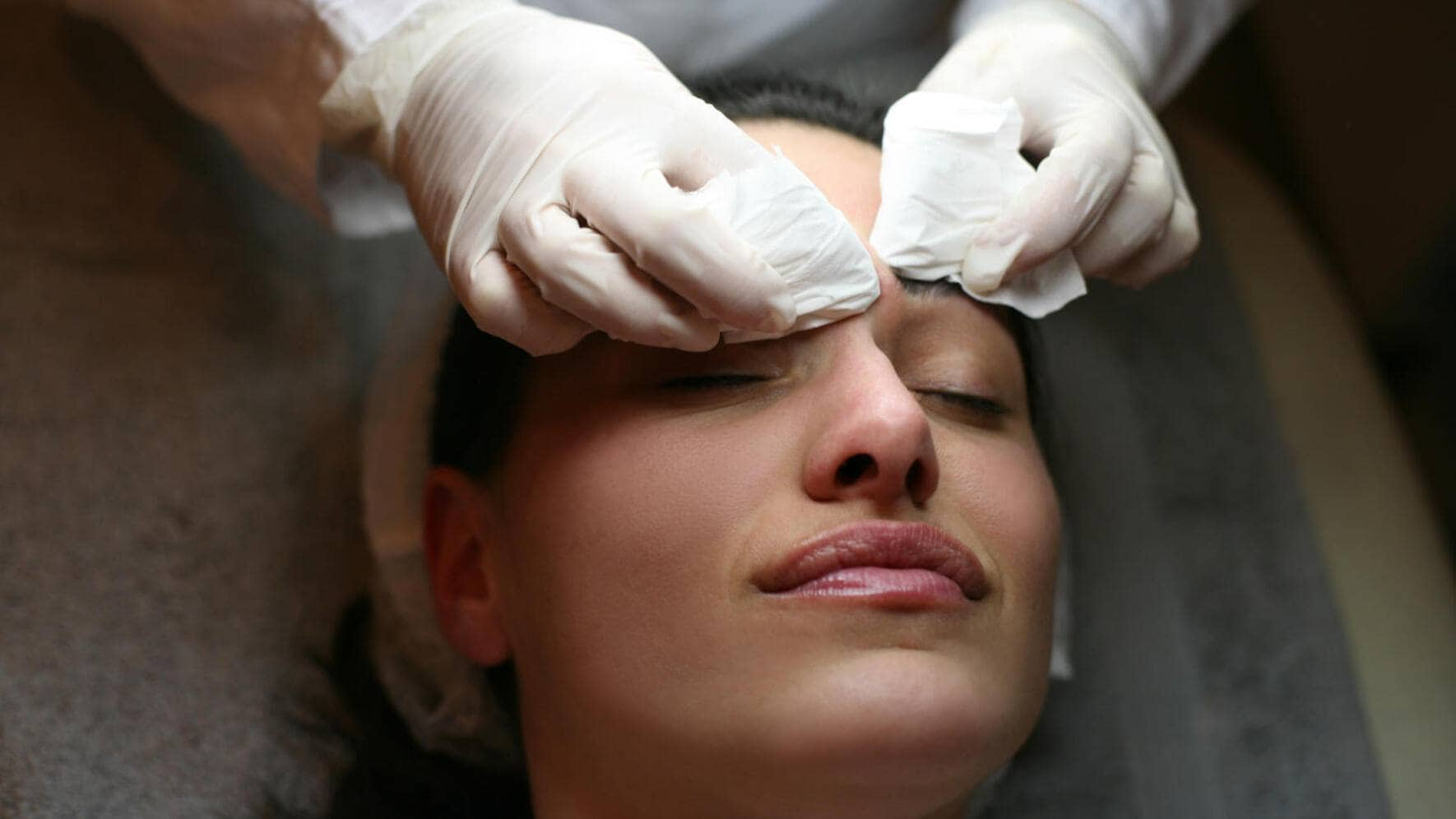 Midsection of a beautician cleaning young females face.
