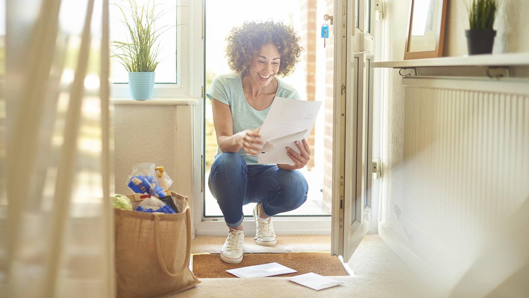 a woman returns home from the shops and finds some letters on the mat . She bends down to open them and smiles at what she is reading