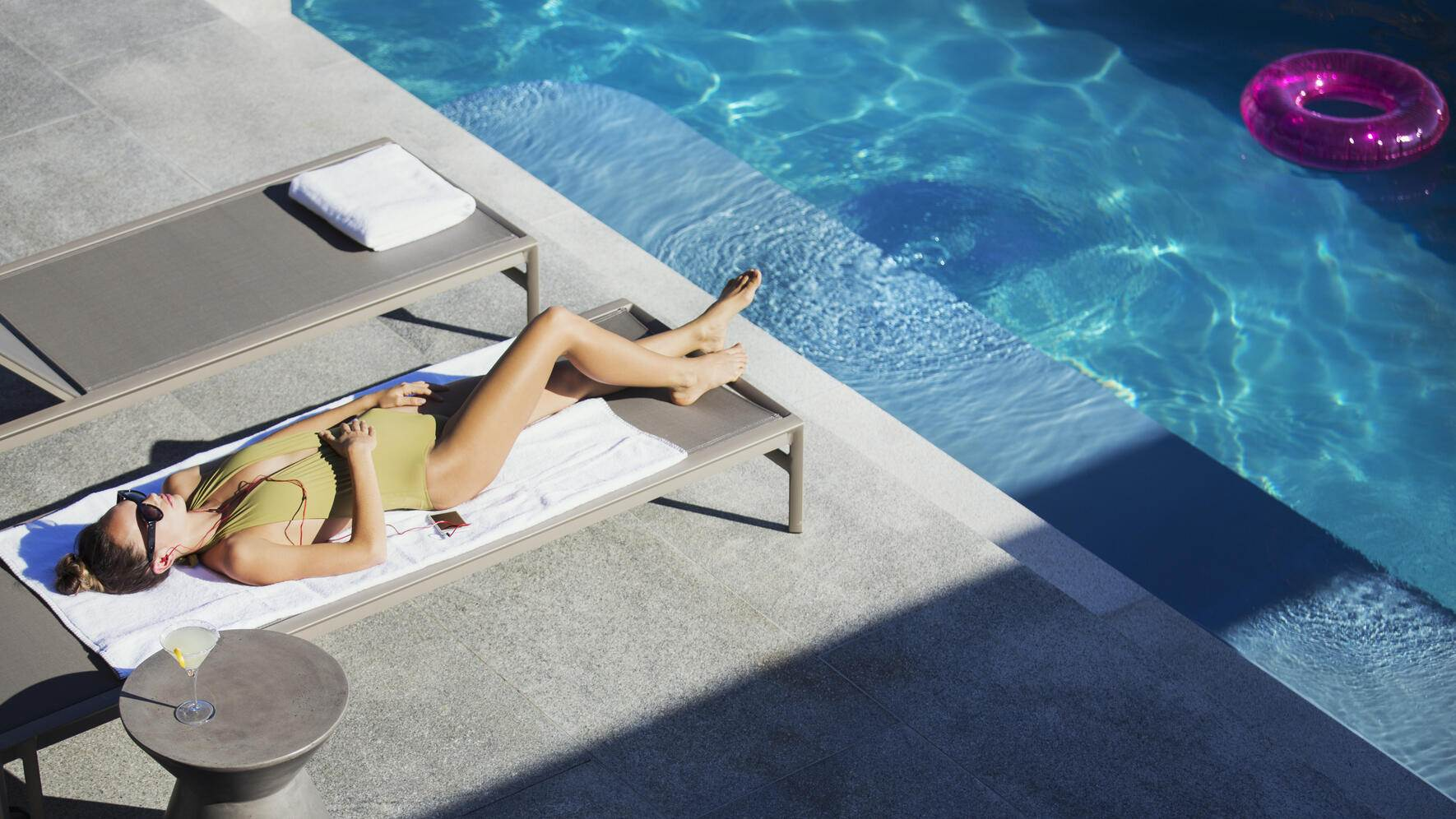 Woman in bathing suit sunbathing on lounge chair at sunny luxury poolside