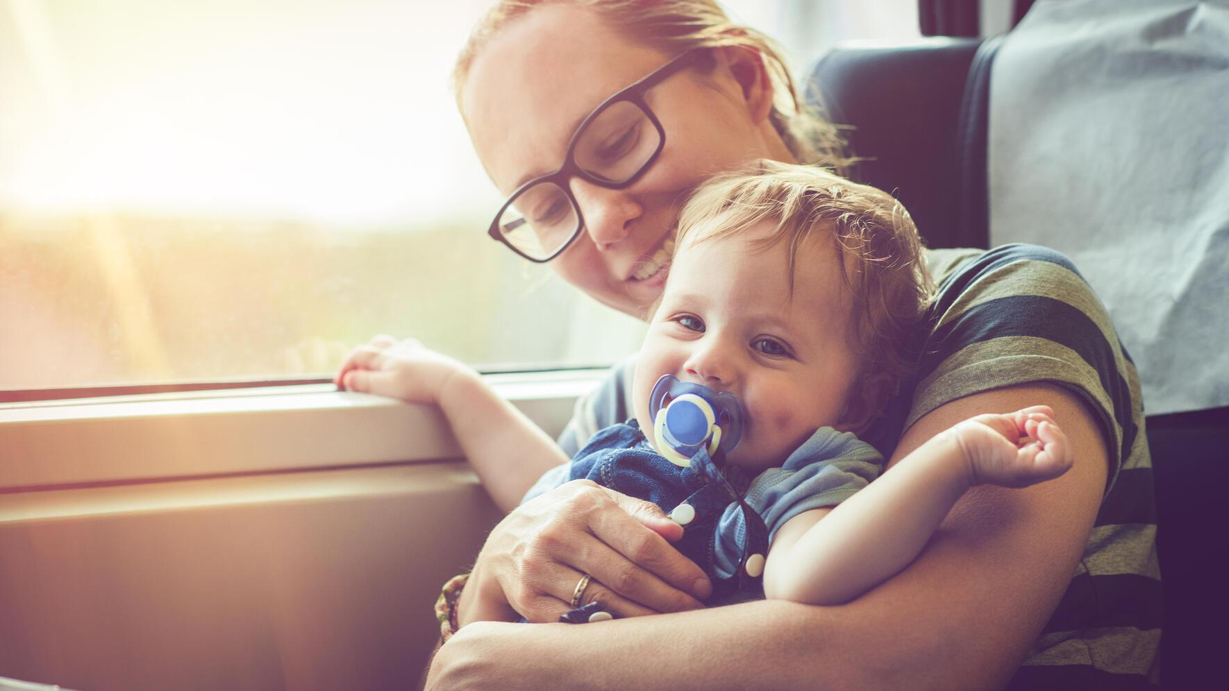 Happy mother and her baby bot travelling in train in summer