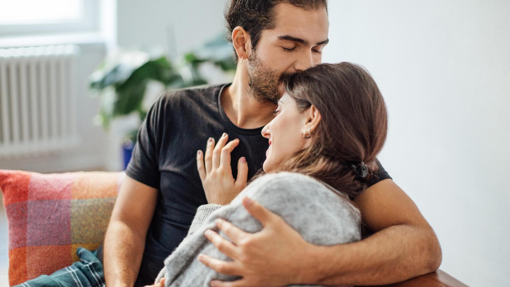 Young man embracing girlfriend while kissing on her forehead in living room at home