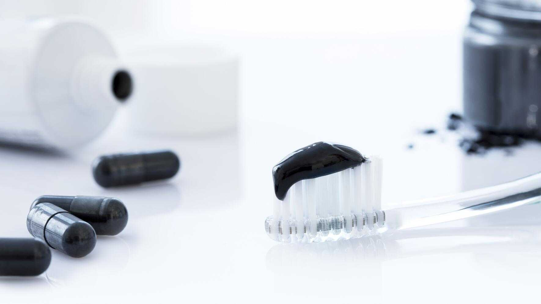 Charcoal toothpaste on a toothbrush.