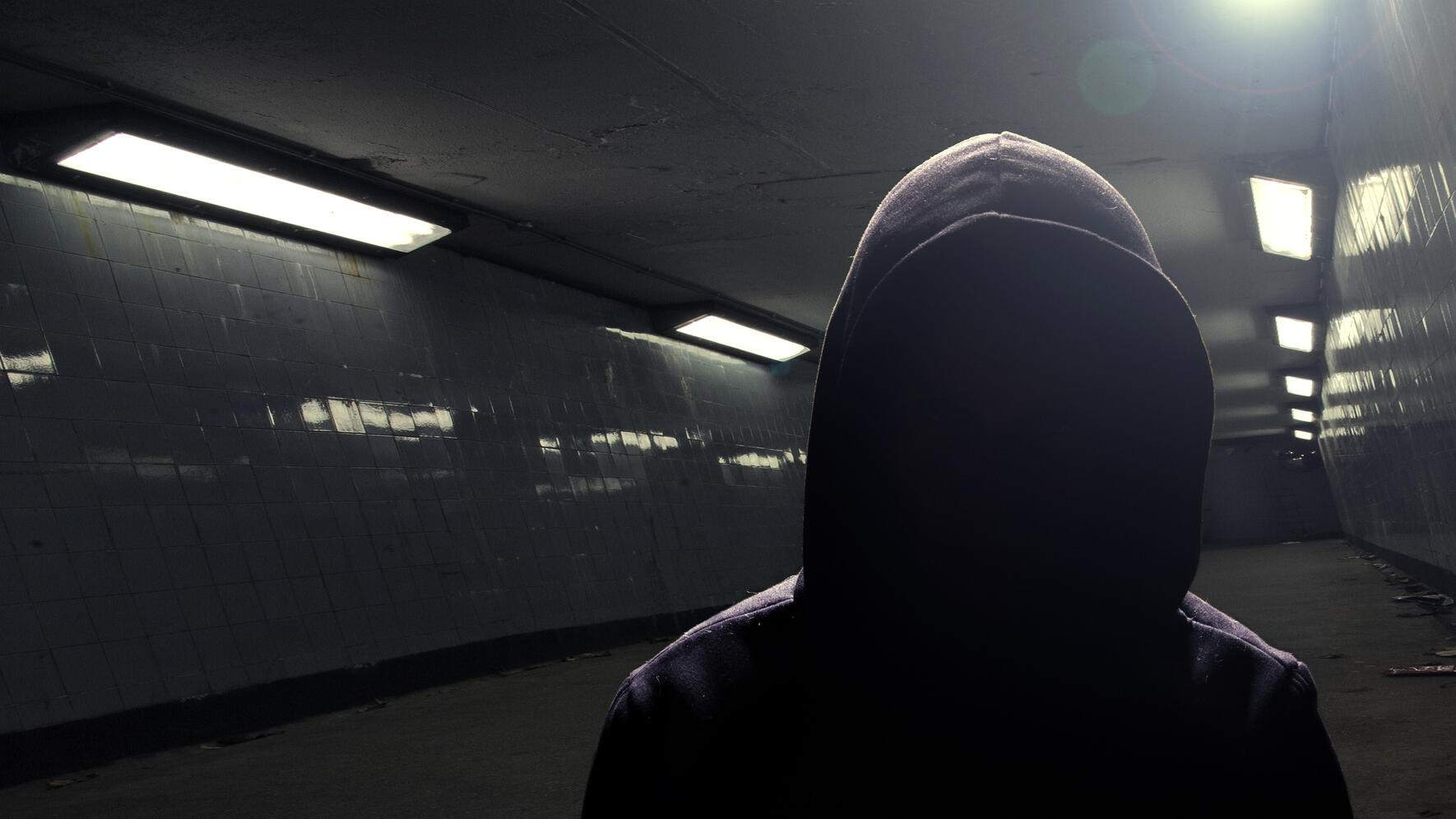Silhouette of a man wearing a hooded shirt standing in an underpass.