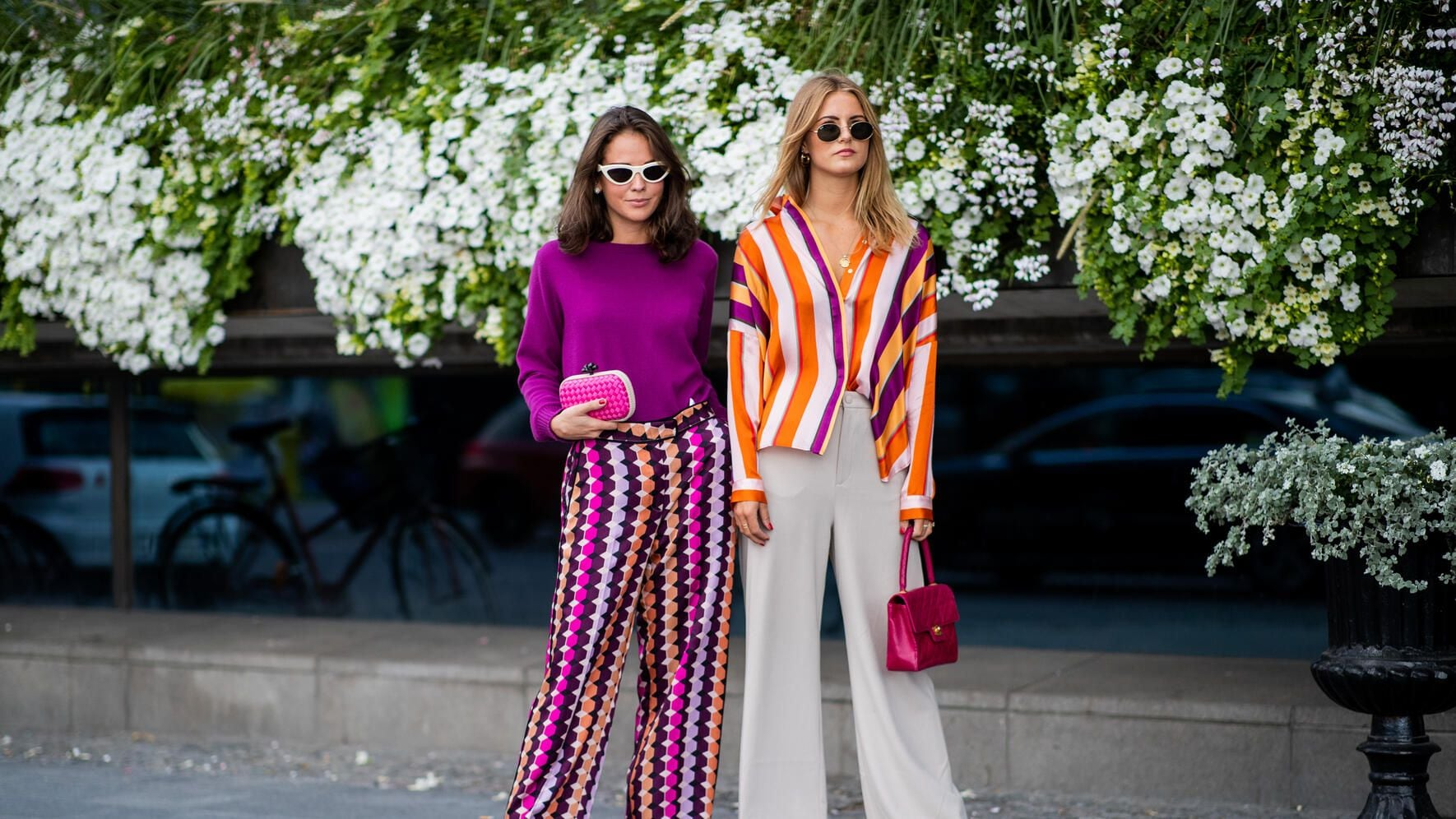 STOCKHOLM, SWEDEN - AUGUST 28: Guests wearing purple knit, multi colored wide leg pants, pink clutch and a guest wearing striped button shirt, wide leg pants, red Chanel bag seen during Stockholm Runway SS19 on August 28, 2018 in Stockholm, Sweden. (Photo by Christian Vierig/Getty Images)