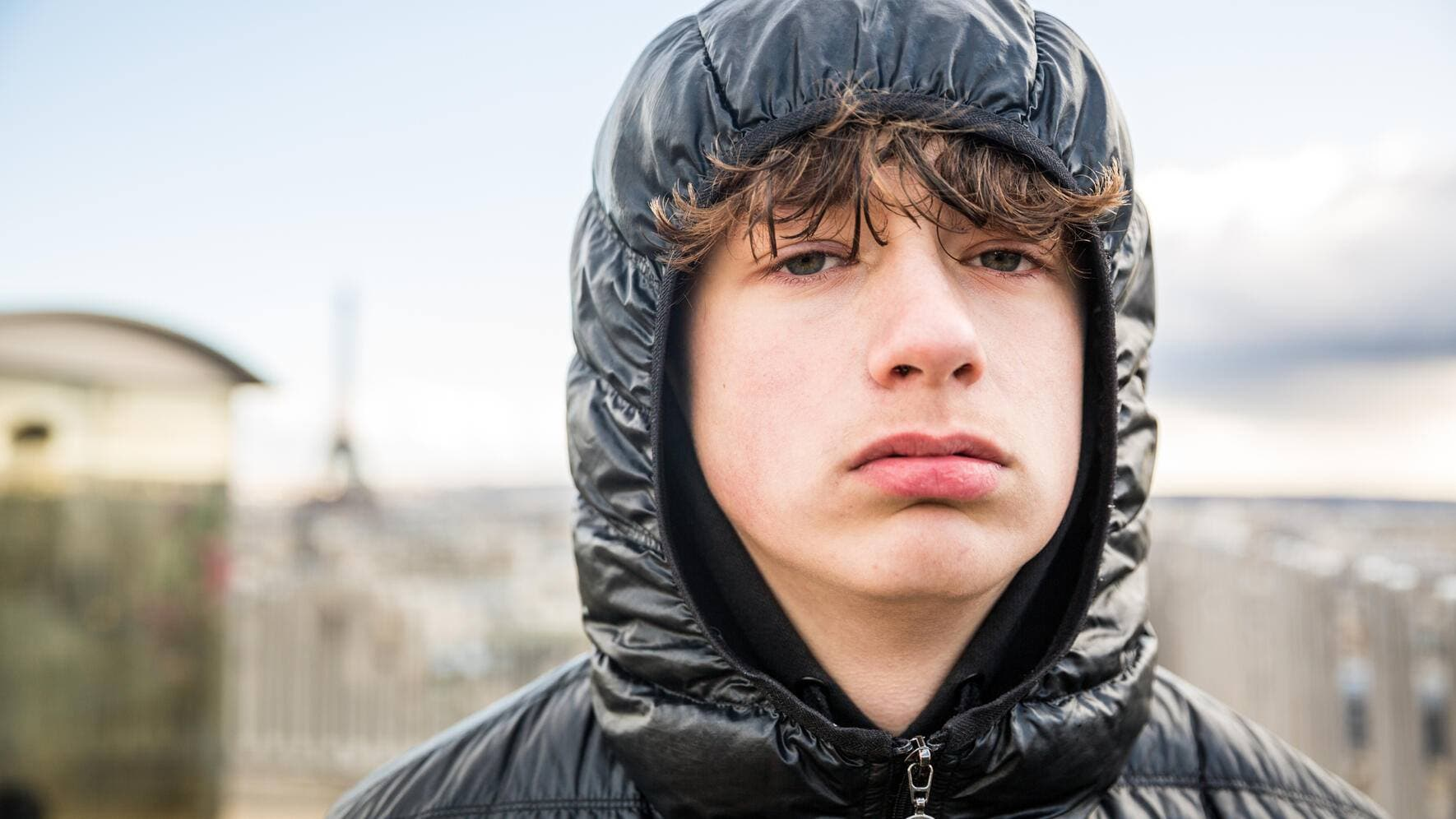 Teenage boy looking at camera wearing a hood with Paris cityscape background