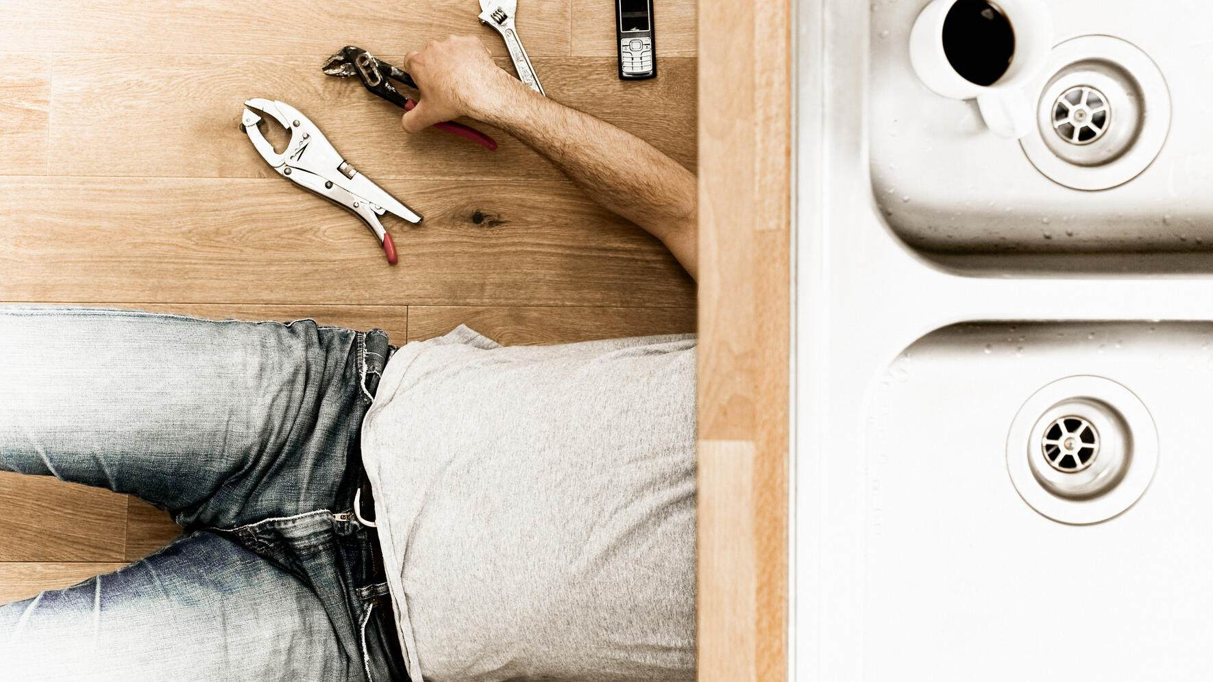 Plumber laying on floor under sink with tools and mobile phone