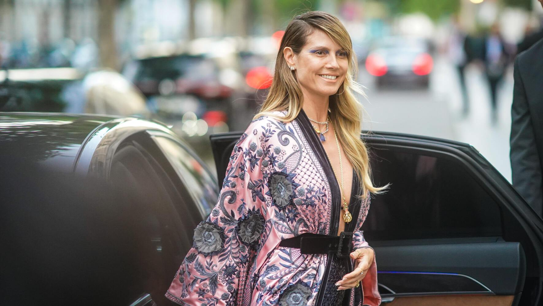 PARIS, FRANCE - JUNE 30: Heidi Klum wears earrings, necklaces, a lustrous beaded and embroidered floral print pale-pink kimono-style long jacket, a black velvet belt, nacreous sequined deep blue  pants, outside AMFAR dinner, during Paris Fashion Week - Haute Couture Fall/Winter 2019/2020, on June 30, 2019 in Paris, France. (Photo by Edward Berthelot/Getty Images)