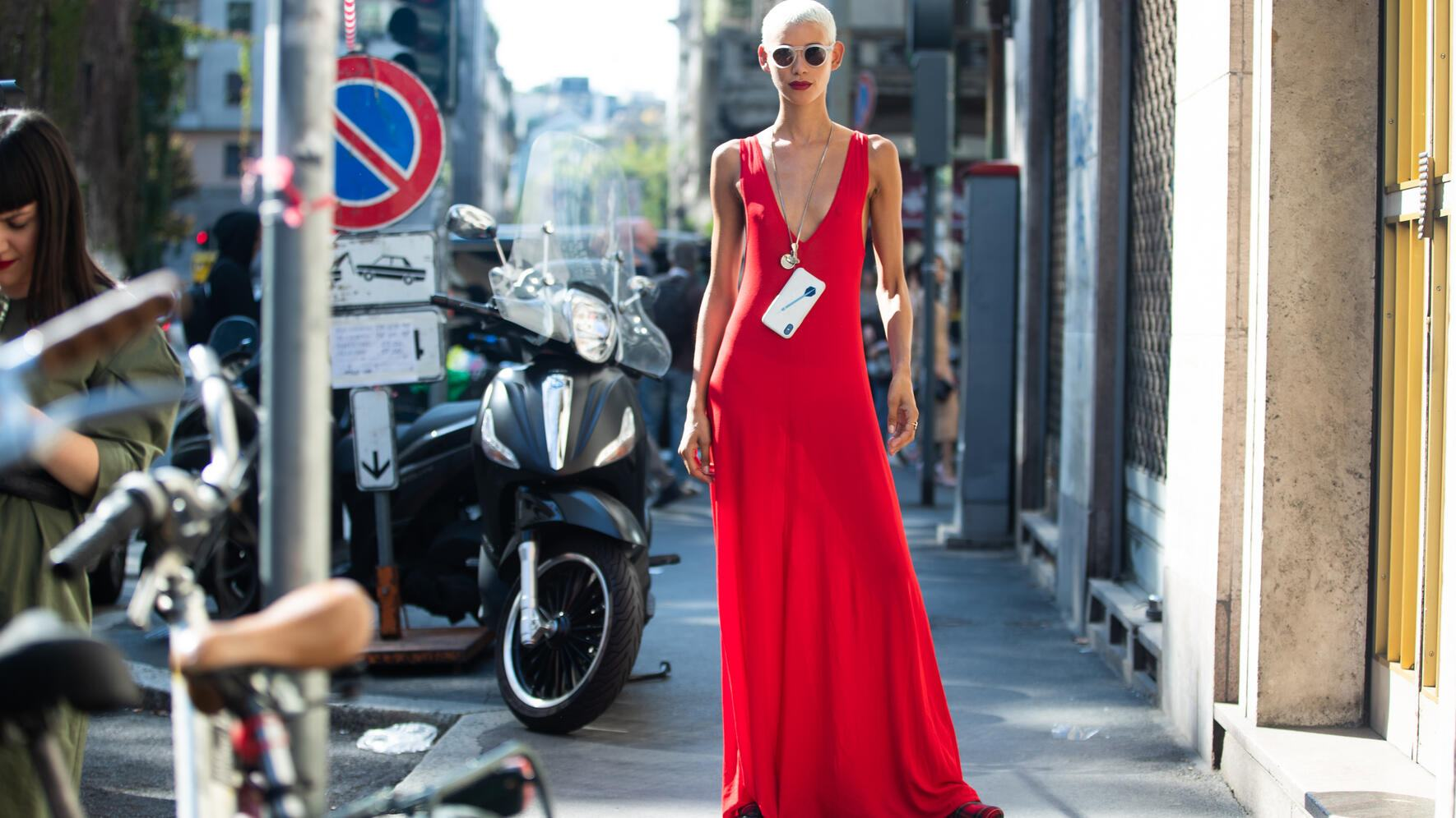 MILAN, ITALY - SEPTEMBER 23:  Model Dilone wears white sunglasses, a red sleeveless dress and her iPhone around her neck after the Dolce & Gabbana show during Milan Fashion Week Spring/Summer 2019 on September 23, 2018 in Milan, Italy.