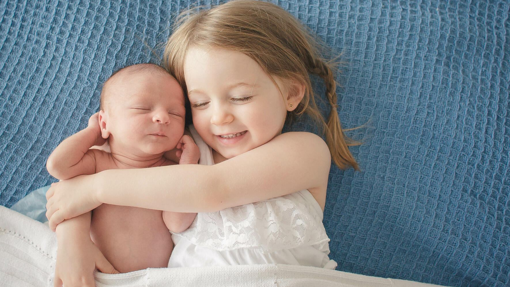 Preschool-aged toddler girl hugs her newborn baby brother on top of a blue blanket and under a white blanket.  She is smiling with her eyes closed while the baby sleeps contentedly.