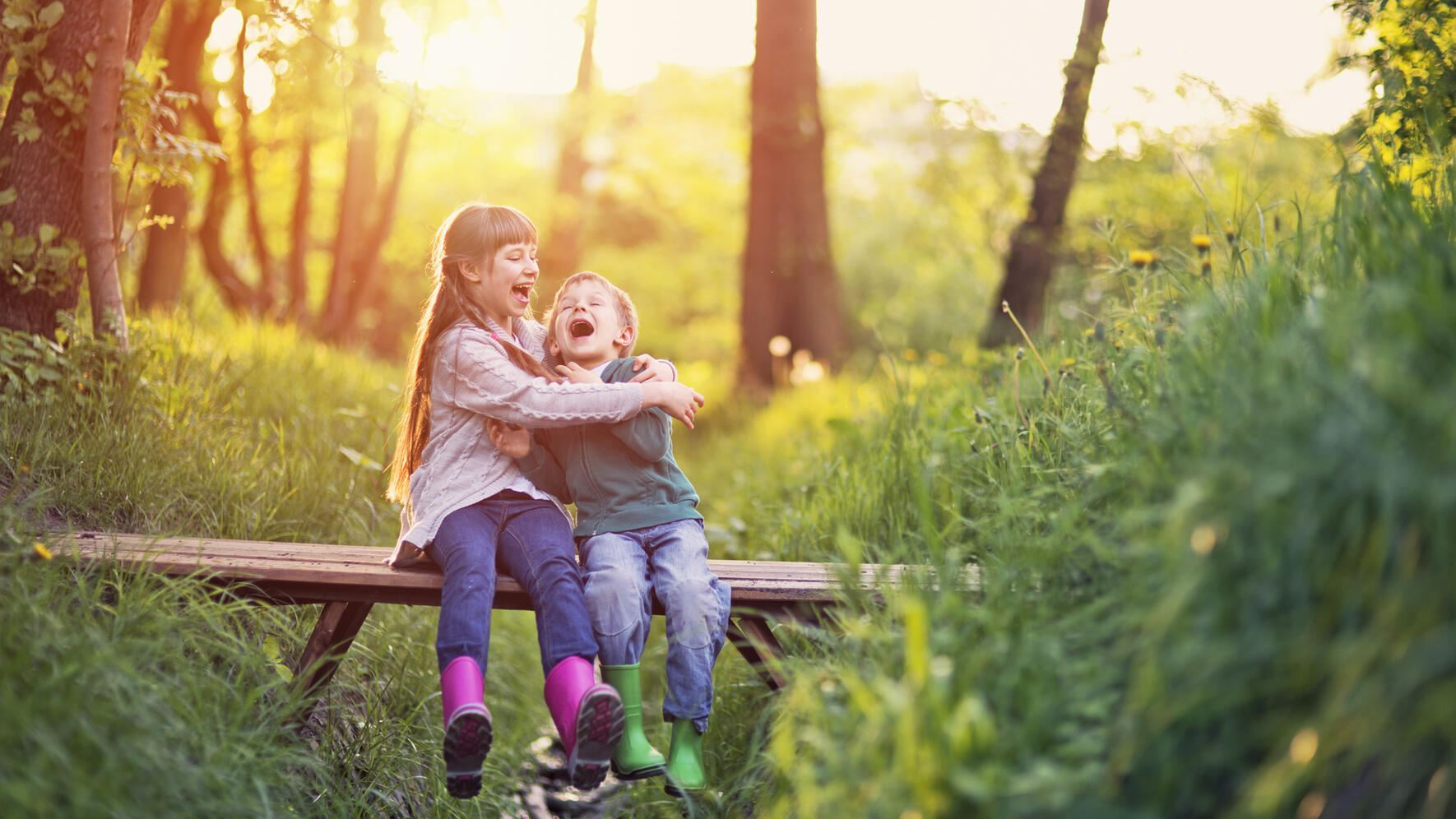 Little boy aged 5 and his elder sister aged 9 are sitting on the small bridge in the forest. They are enjoying beautiful nature and the sunset, laughing happily.