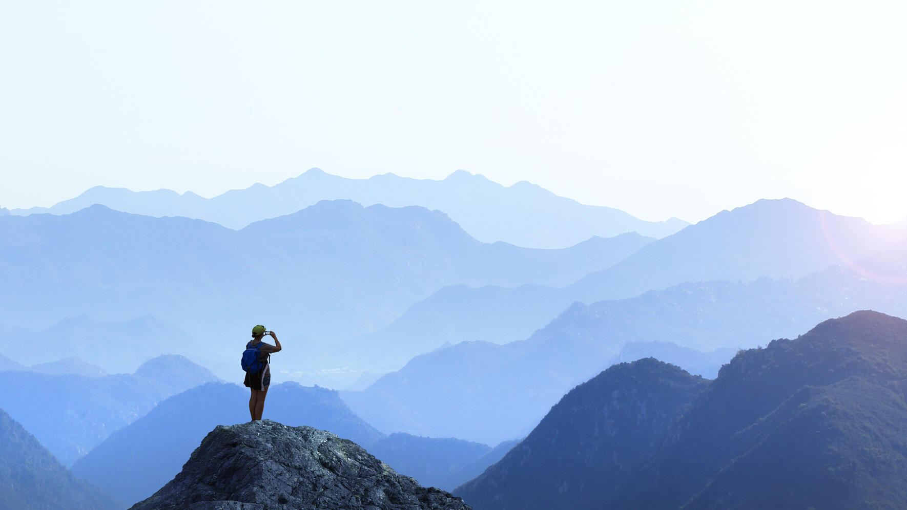 A female hiker stands on top of a rocky promontory as she uses her mobile phone to take a picture of the setting sun on the distant horizon. A series of mountain ridges seem to disappear into the distance as the haze obscures the details creating a graphic outline of the various layers of ridge lines.