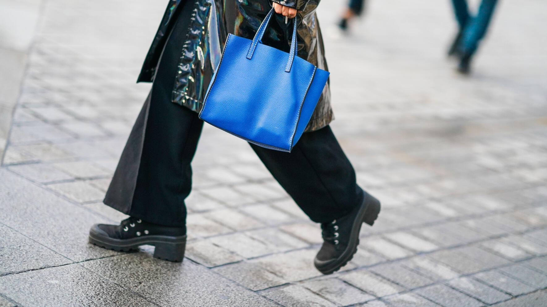 PARIS, FRANCE - OCTOBER 01: A guest wears a black pvc trench rain coat, a blue bag, flare pants, black shoes, outside Louis Vuitton, during Paris Fashion Week - Womenswear Spring Summer 2020, on October 01, 2019 in Paris, France. (Photo by Edward Berthelot/Getty Images)