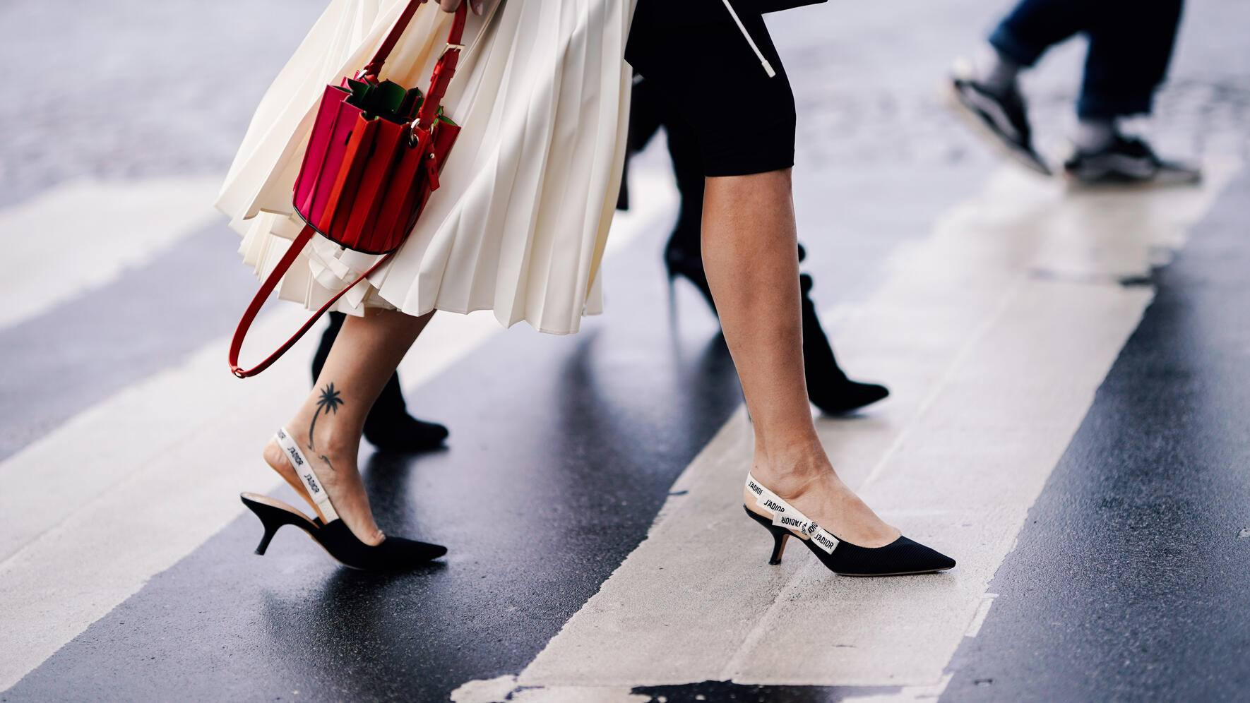 PARIS, FRANCE - MARCH 02: A guest wears a red pleated bucket bag, black J'Adior Dior shoes, outside Haider Ackermann, during Paris Fashion Week Womenswear Fall/Winter 2019/2020, on March 02, 2019 in Paris, France. (Photo by Edward Berthelot/Getty Images)