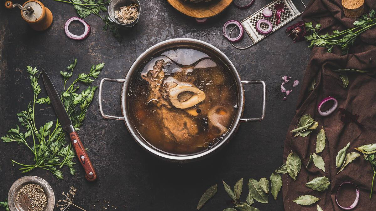 Cooking pot with beef bone broth or stock on dark rustic table background with ingredients, bowls, knife and kitchenware , top view. Cooking preparation , step by step