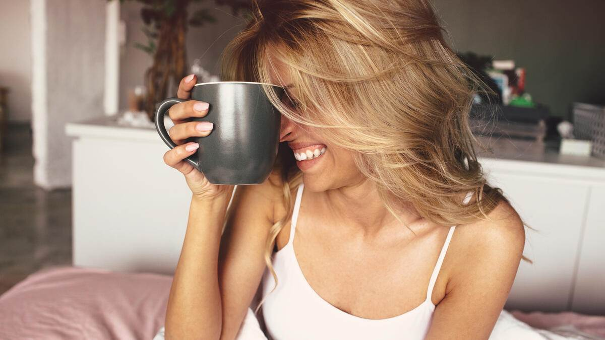 Young smiling woman having a cup of coffee in her bed, right after waking up