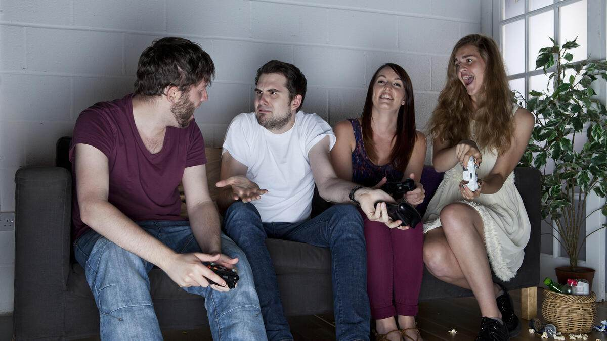 A group of young men and women with various expressions of happiness, anger and confusion playing Sony PlayStation 3 video games on a sofa, taken on July 9, 2013. (Photo by Philip Sowels/Future Publishing via Getty Images)