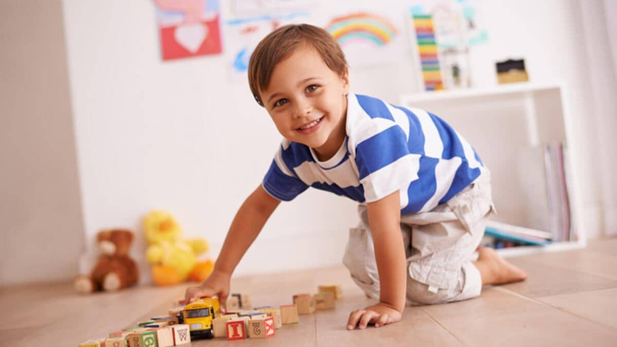 Portrait of a cute little boy playing with his building blocks and toys in his room