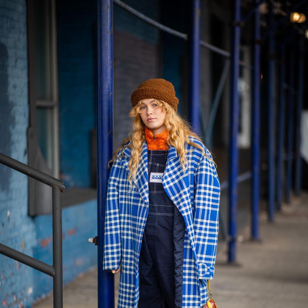 NEW YORK, NEW YORK - FEBRUARY 11: A guest is seen wearing denim overall, plaid coat, teddy beanie outside Zadig & Voltaire during New York Fashion Week Autumn Winter 2019 on February 11, 2019 in New York City. (Photo by Christian Vierig/Getty Images)