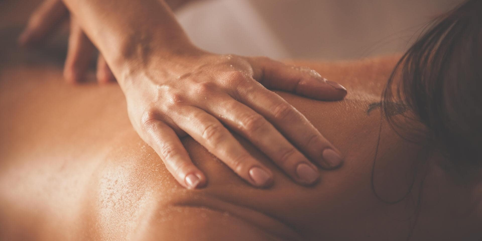Close-up shot of beautician rubbing body scrub on woman's back and shoulders.