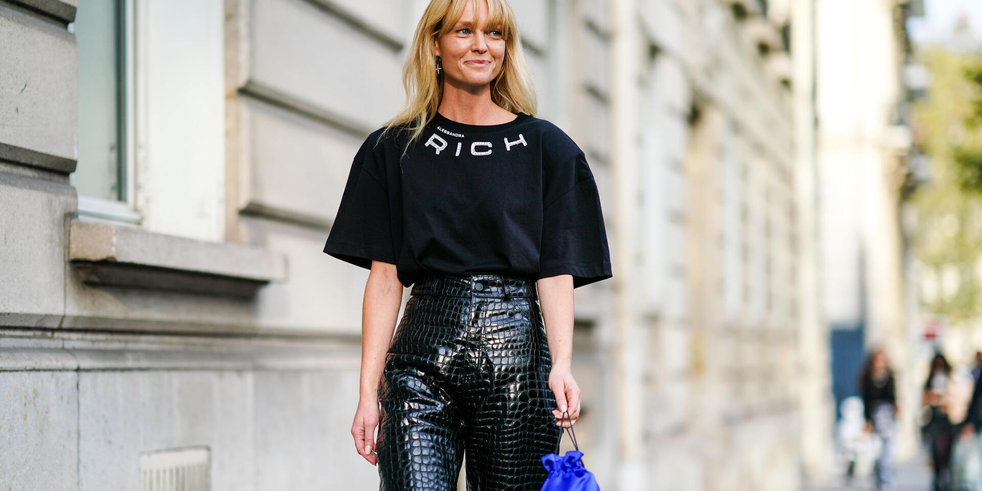 PARIS, FRANCE - SEPTEMBER 27: Jeanette Madsen wears earrings, a black Alessandra Rich  t-shirt, shiny black crocodile pattern high waist leather pants, a blue fringy bag, outside Alessandra Rich, during Paris Fashion Week - Womenswear Spring Summer 2020 on September 27, 2019 in Paris, France. (Photo by Edward Berthelot/Getty Images)