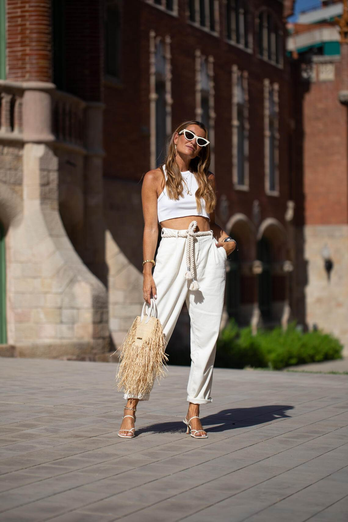 BARCELONA, SPAIN - JUNE 27: A guest is seen on the street attending 080 Barcelona Fashion Week wearing white crop top, white high-waist pants and a Jacquemus straw bag on June 27, 2019 in Barcelona, Spain. (Photo by Matthew Sperzel/Getty Images)