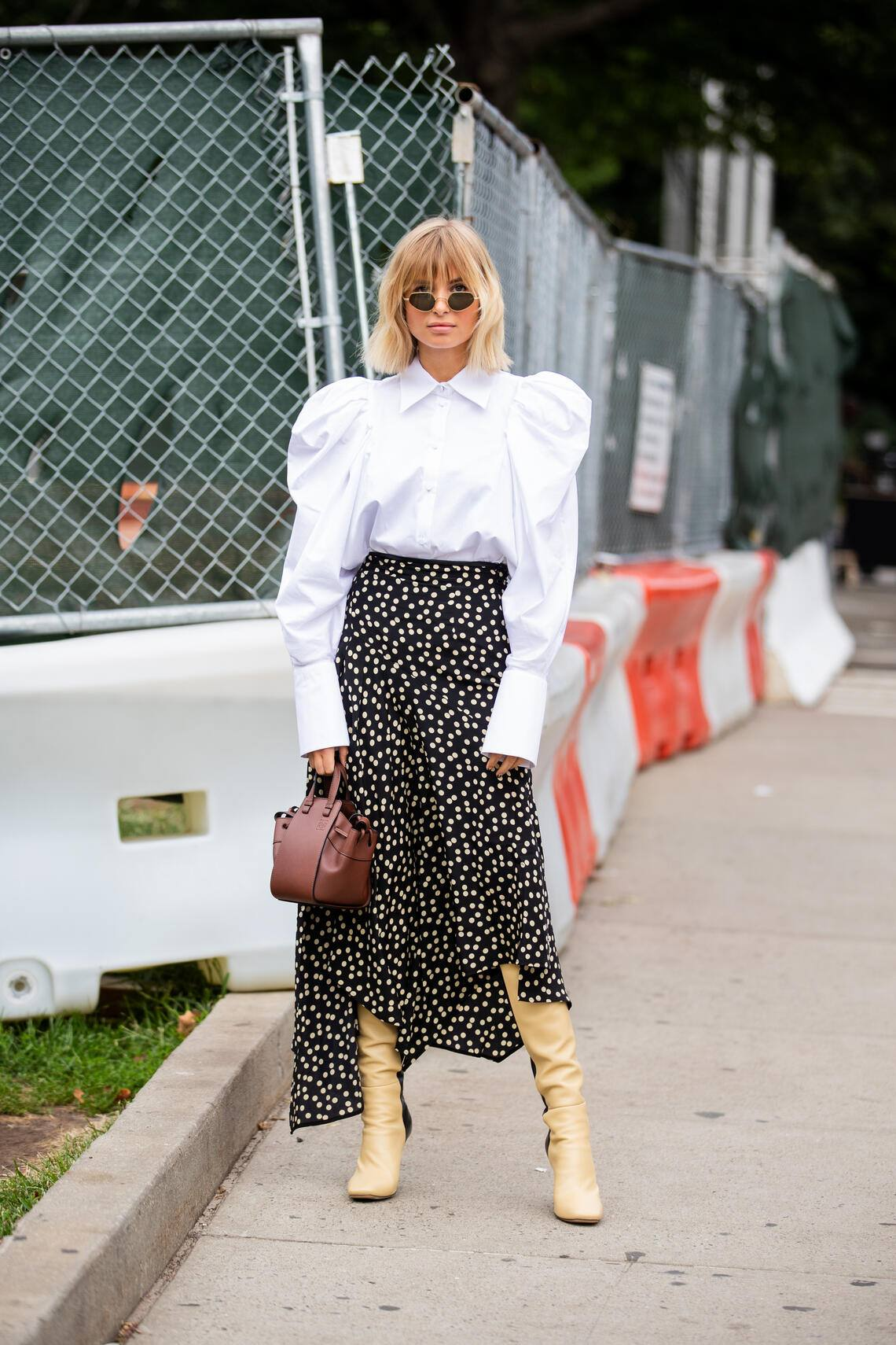 NEW YORK, NEW YORK - SEPTEMBER 08: Xenia Adonts is seen wearing white blouse, asymmetric skirt, boots, brown bag outside Tory Burch during New York Fashion Week September 2019 on September 08, 2019 in New York City. (Photo by Christian Vierig/Getty Images)