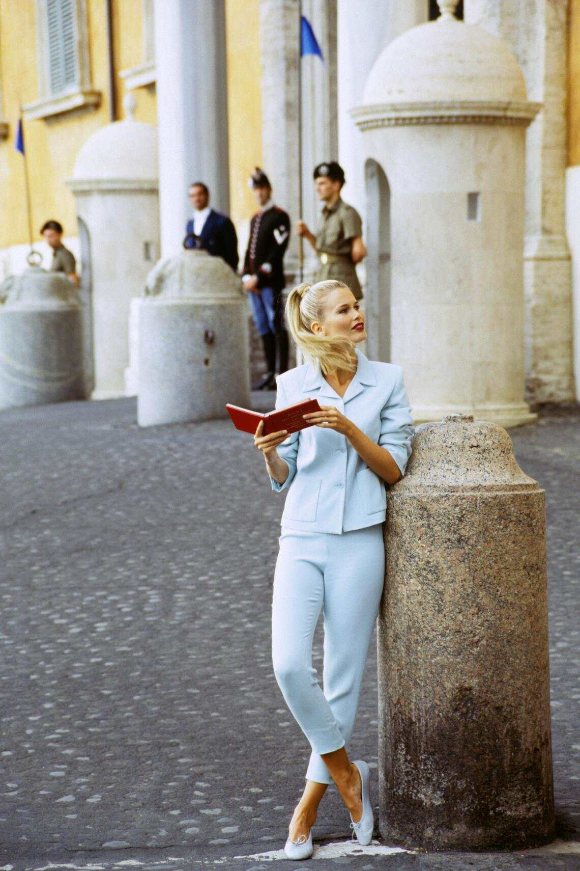 ITALY - DECEMBER 1:  Model Claudia Schiffer, with book on Roman street, wearing capri pants and spencer-style jacket in aqua blue, by Mark Eisen  CREDIT MUST READ: Arthur Elgort/Conde Nast via Getty Images. (Photo by Arthur Elgort/Conde Nast via Getty Images)