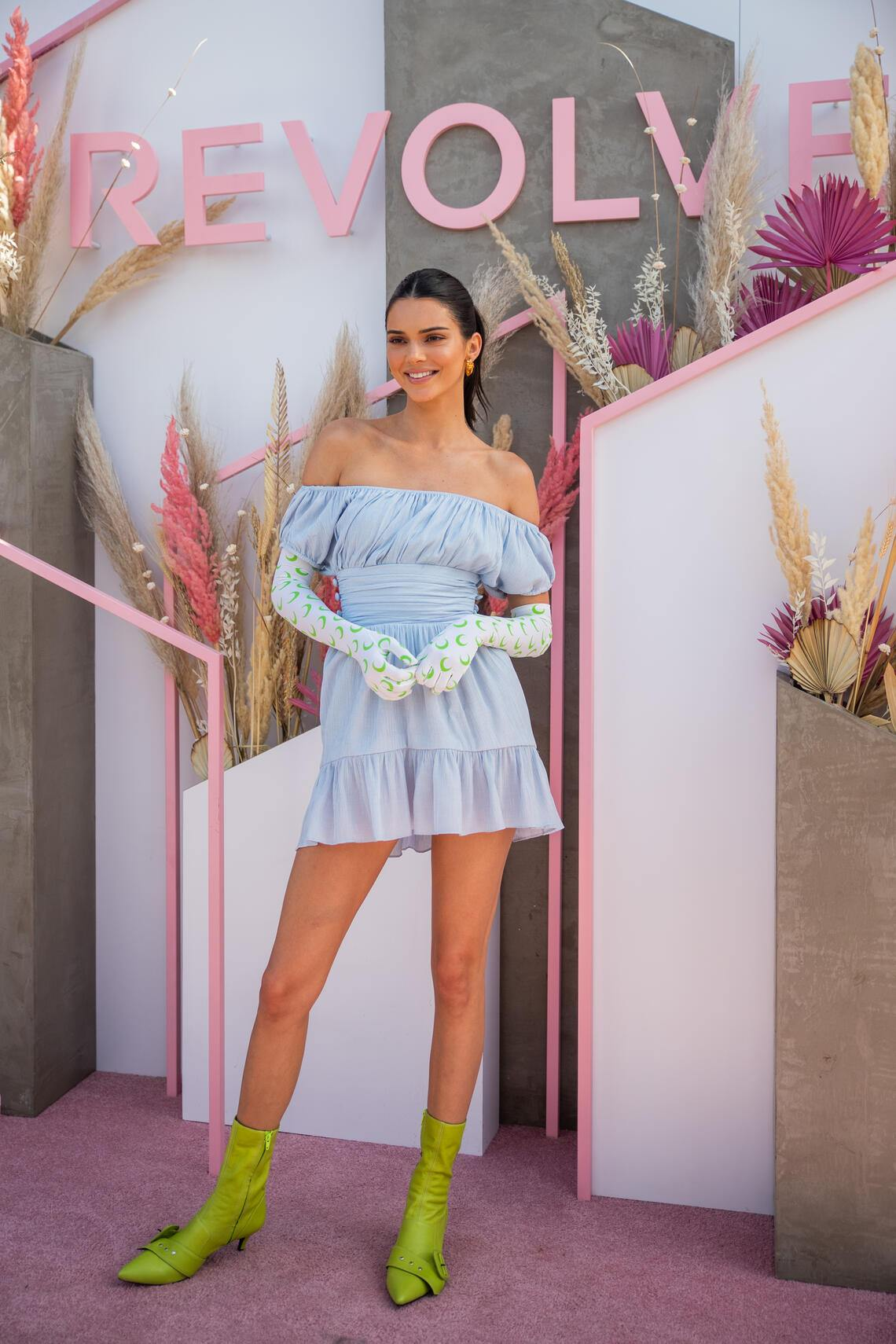 LA QUINTA, CALIFORNIA - APRIL 14: Kendall Jenner is seen wearing blue off shoulder dress, gloves with print, green sock boots at Revolve Festival during Coachella Festival on April 14, 2019 in La Quinta, California. (Photo by Christian Vierig/Getty Images)