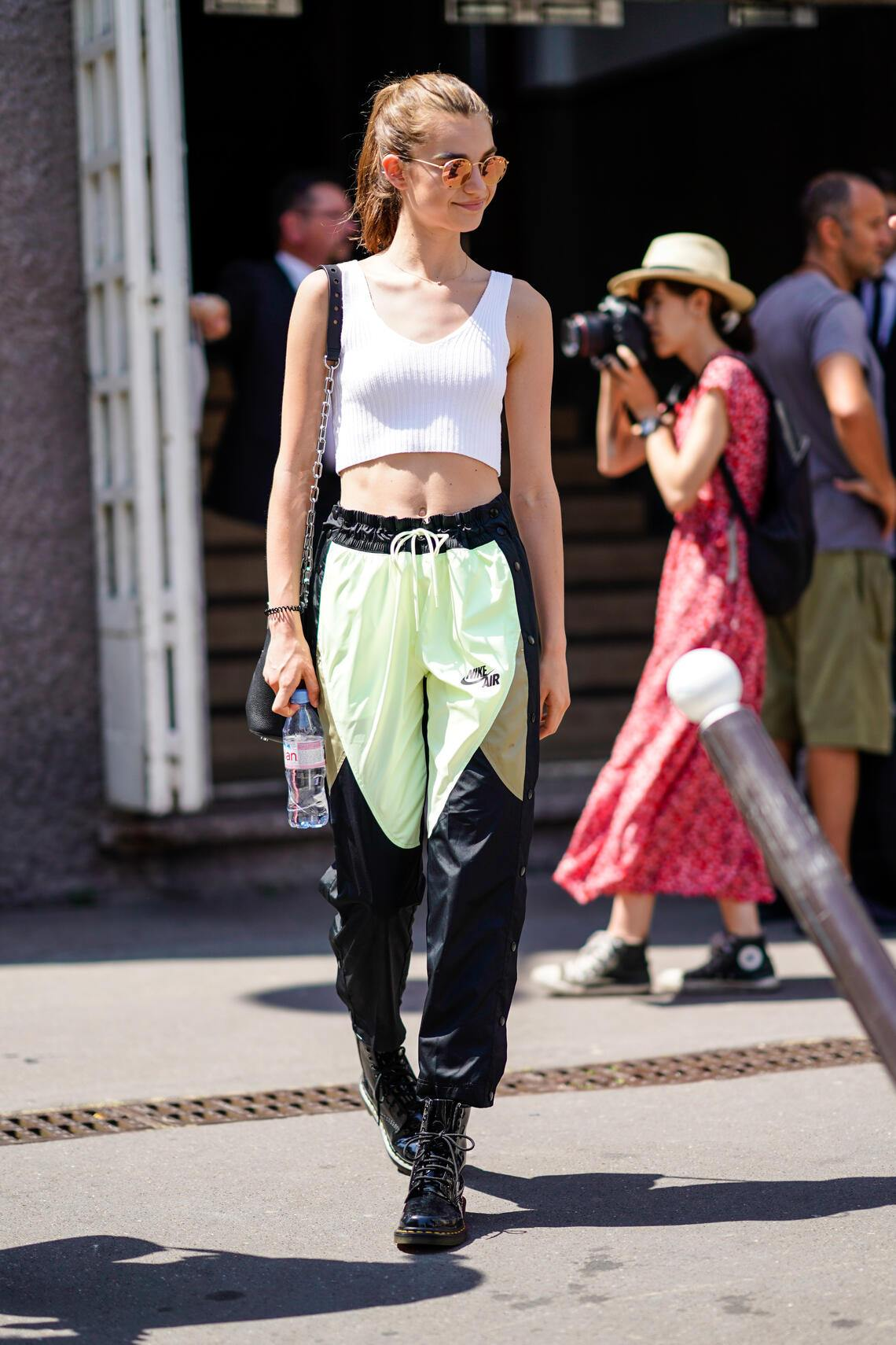 PARIS, FRANCE - JULY 01: A model wears sunglasses, a white cropped bare belly top, Nike pants, black boots , outside Acne Studios, during Paris Fashion Week - Womenswear Fall Winter 2019, on July 1, 2018 in Paris, France.  (Photo by Edward Berthelot/Getty Images)