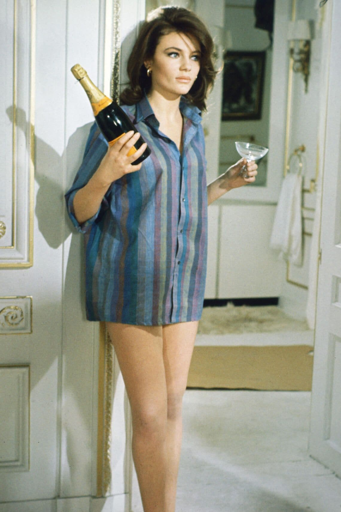 Jacqueline Bisset, British actress, wearing a shirt with vertical stripes, and holding a bottle of champagne and a champagne coupe, in a publicity still issued for the film, 'Bullitt', 1968. The thriller, directed by Peter Yates (1929-2011), starred Bisset as 'Cathy'. (Photo by Silver Screen Collection/Getty Images)