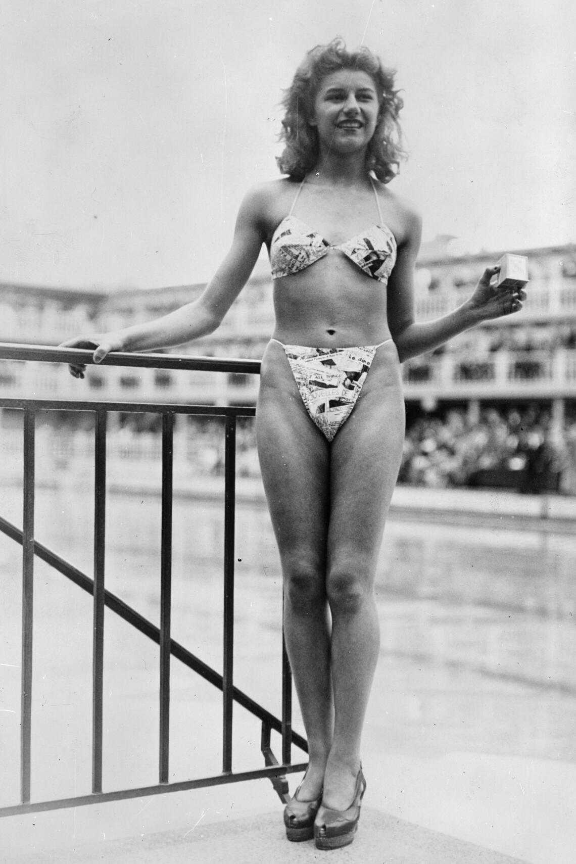 The new 'Bikini' swimming costume (in a newsprint-patterned fabric), which caused a sensation at a beauty contest at the Molitor swimming pool in Paris. Designer Louis Reard was unable to find a 'respectable' model for his costume and the job of displaying it went to 19-year-old Micheline Bernardini, a nude dancer from the Casino de Paris. She is holding a small box into which the entire costume can be packed. Celebrated as the first bikini, Luard's design came a few months after a similar two-piece design